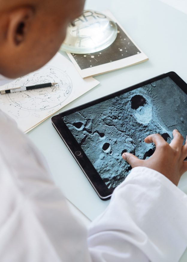 Students zooms in on an image of the moon on a tablet.
